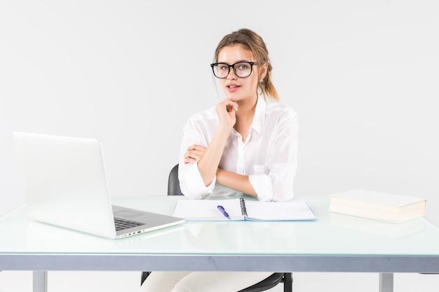 Jonge onderneemsterzitting bij een bureaulijst met laptop, die de camera bekijkt die op witte achtergrond wordt geïsoleerd