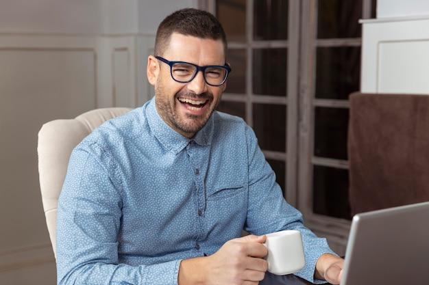 Jonge ondernemende man met bril en overhemd glimlacht en drinkt koffie tijdens het werken vanuit huis