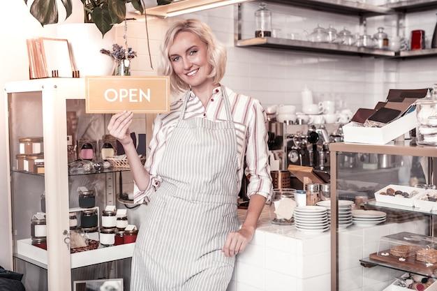 Jonge ondernemer. blije positieve vrouw die naar u glimlacht tijdens het openen van haar café