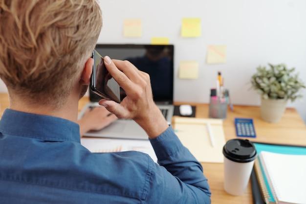 Jonge ondernemer die e-mails op laptop controleert en telefoontje van zijn collega beantwoordt, uitzicht vanaf de achterkant