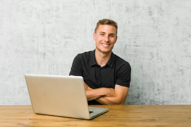 Jonge ondernemer die met zijn laptop aan een bureau werkt dat en pret lacht heeft.