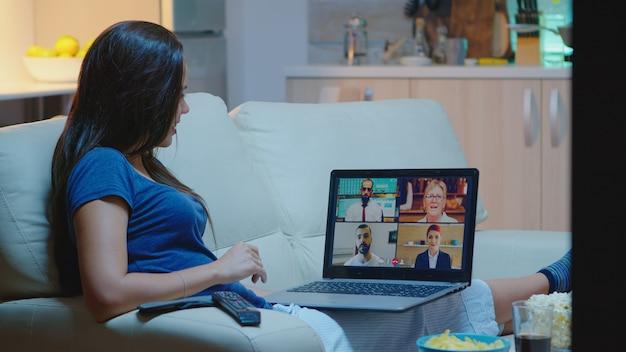 Jonge ondernemer die vanuit huis werkt met een laptop die pijamas draagt die in de woonkamer voor de tv zit. externe werknemer met online vergadering, videoconferentie overleg met collega's die laptop gebruiken.