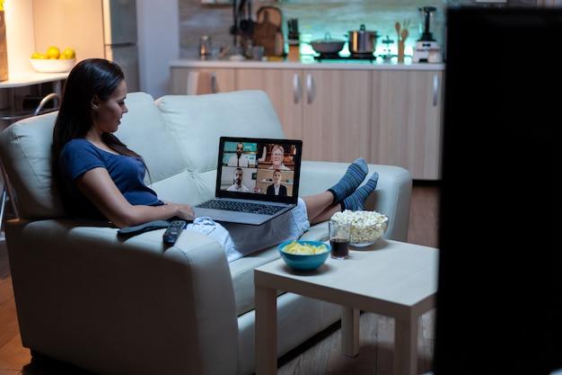 Jonge ondernemer die vanuit huis werkt met een laptop die pijamas draagt en in de woonkamer voor de tv zit