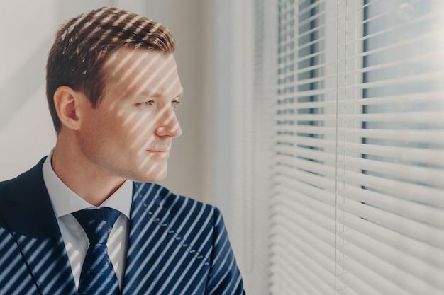 Jonge ondernemer in rijk pak, denkt aan de toekomst van zijn bedrijf