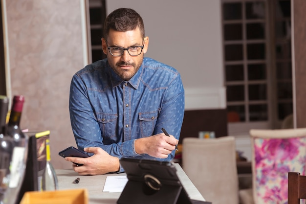 Jonge ondernemer met glazen en overhemd die op de staaf van een cocktailbar leunen