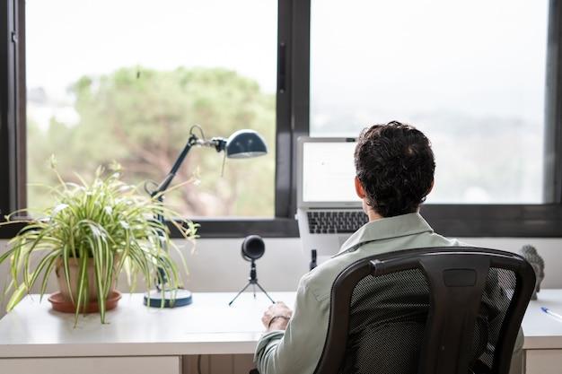 Jonge ondernemer werkt vanuit huis in zijn kantoor met de computer voor een raam