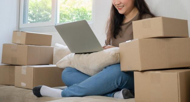 Jonge ondernemer, zittend op de bank en thuis werken en bestellingen controleren