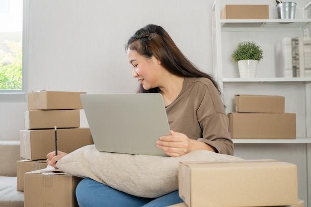 Jonge ondernemer, zittend op de bank en thuis werken en bestellingen van klanten controleren via laptop