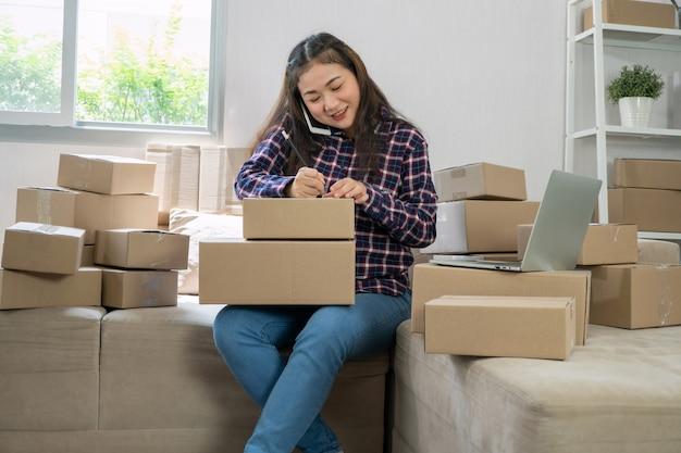 Jonge ondernemer, zittend op de bank en thuis werken. telefonisch bestellingen ontvangen van klanten