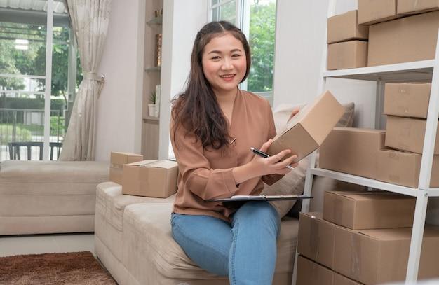 Jonge ondernemer, zittend op de bank en thuis werken. ze glimlacht en houdt een verpakking vast