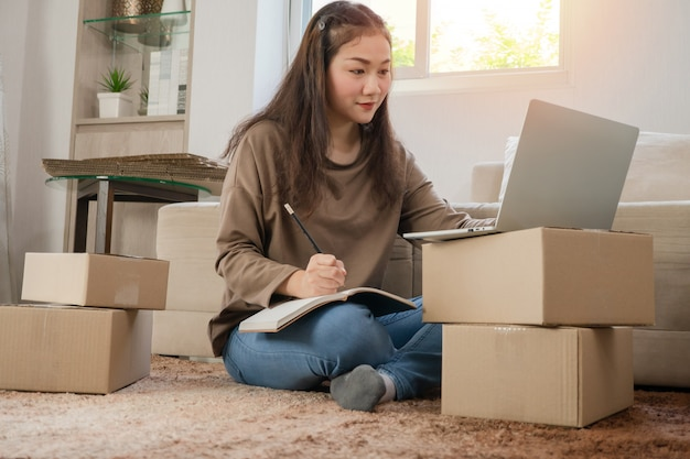 Jonge ondernemer, zittend op de vloer en thuis werken.
