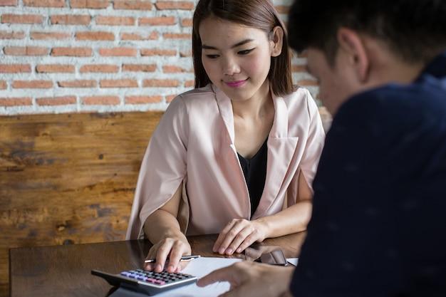 Jonge ondernemers berekenen inkomstenuitgaven voor het zakendoen met partners.