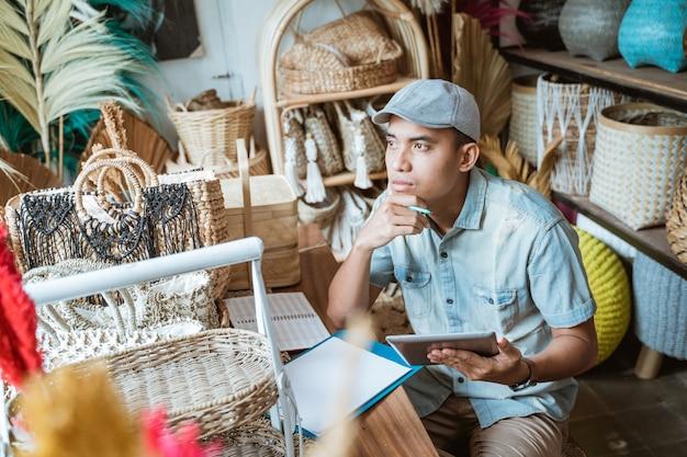 Jonge ondernemers denken serieus na bij het maken van aantekeningen met een balpen terwijl ze een schrijfblok tegen een handgemaakt papier gebruiken