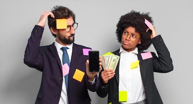 Jonge ondernemers die zich in verwarring en verwardheid voelen, hun hoofd krabben en naar de zijkant kijken. humoristisch bedrijfsconcept
