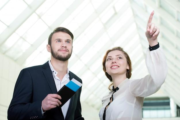 Jonge ondernemers met een koffer komen naar airoport.