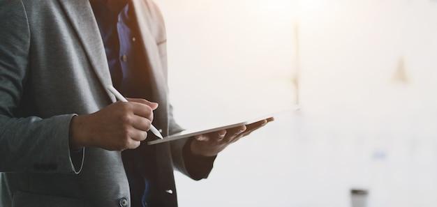 Jonge ondernemers werken aan zijn project tijdens het gebruik van tablet in moderne kantoren