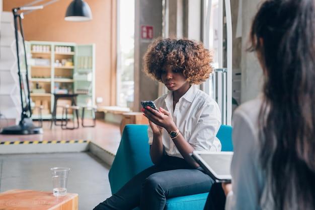 Jonge ondernemers werken met smart-apparaat in moderne kantoor