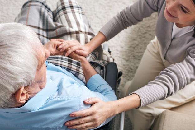 Jonge ondersteunende vrouwelijke verzorger zit door senior man in rolstoel en houdt haar hand op zijn schouder terwijl hij hem troost