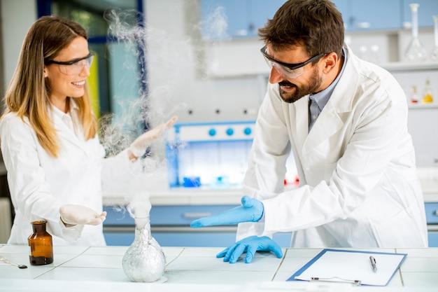 Jonge onderzoekers experimenteren met rook op een tafel van een chemisch laboratorium