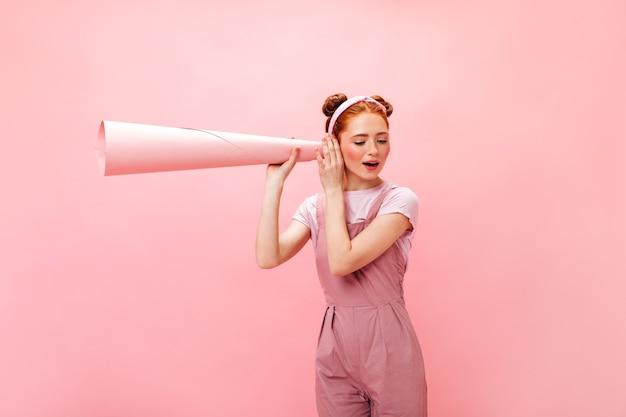 Jonge ondeugende roodharige vrouw in roze jumpsuit luistert met roze buis af.