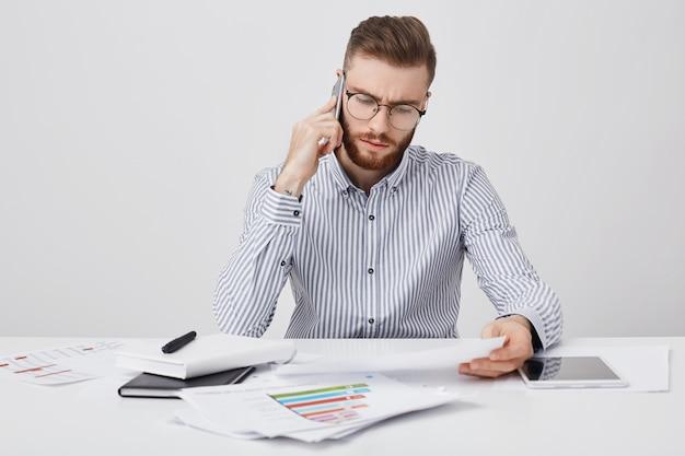 Jonge onervaren mannelijke werknemer met stoppels begrijpt geen informatie in documenten of papier