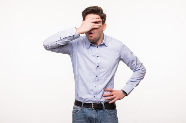 Jonge ongelukkige mens die zijn met de hand behandelde ogen behandelt die op witte ruimte wordt geïsoleerd
