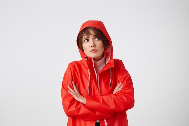 Jonge ongelukkige schattige kortharige dame gekleed in een rode regenjas, met een kap over zijn hoofd, wegkijkend met droevige uitdrukking, staande.