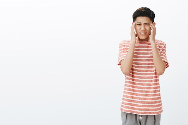 Jonge ongemakkelijke aziatische kerel in gestreept t-shirt voelt zich onder druk gezet en moe, hand in hand op tempels, hoofdpijn of migraine
