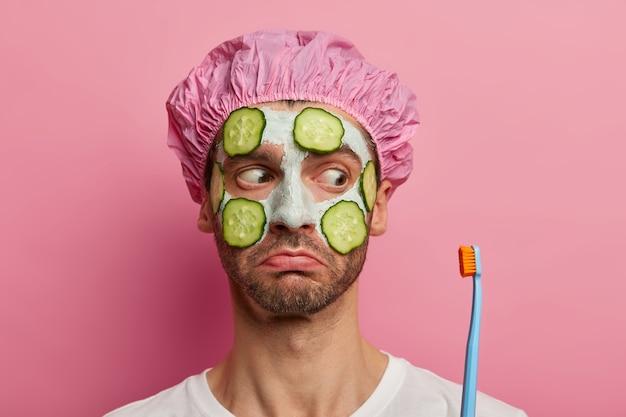 Jonge ongeschoren europese man kijkt droevig naar tandenborstel, wil geen tanden poetsen, voelt zich fris na het nemen van een bad