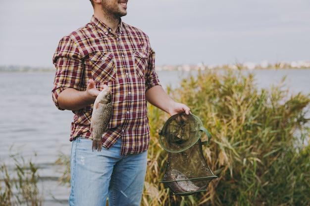 Jonge ongeschoren glimlachende man in geruit hemd houdt in handen groen visnet en vis die hij ving op een oever van een meer in de buurt van struiken en riet. lifestyle, recreatie, vrijetijdsconcept voor vissers