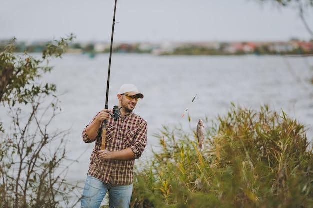 Jonge ongeschoren man in geruit hemd, pet en zonnebril trok een hengel met gevangen vis en verheugt zich op de oever van het meer in de buurt van struiken en riet. lifestyle, recreatie, vrijetijdsconcept voor vissers