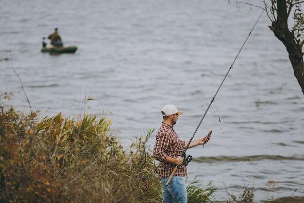 Jonge ongeschoren man in geruit hemd, pet en zonnebril trok een hengel uit en houdt gevangen vis aan de oever van het meer in de buurt van riet tegen de achtergrond van de boot. lifestyle, vrijetijdsconcept voor vissers