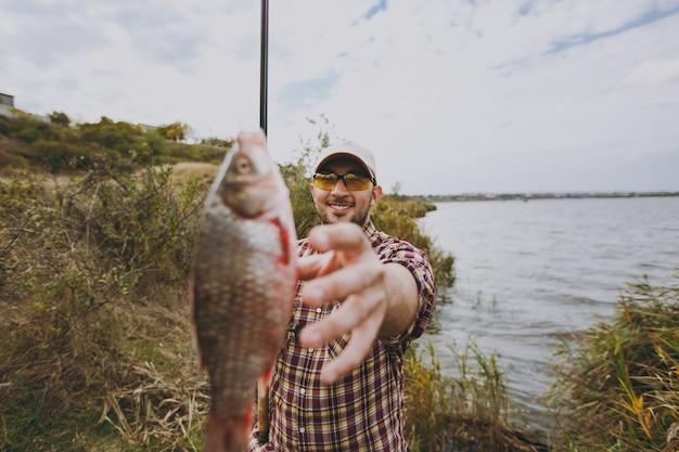 Jonge ongeschoren man in geruit hemd, pet, zonnebril houdt hengel vast en steekt zijn hand uit naar gevangen vis aan de oever van het meer in de buurt van struiken en riet. lifestyle, recreatie, vrijetijdsconcept voor vissers