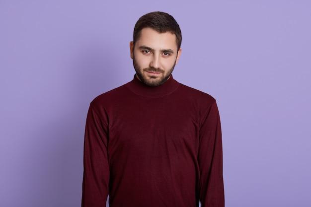 Jonge ongeschoren man met bordeauxrode trui poseren tegen paarse achtergrond met ernstige gezichtsuitdrukking