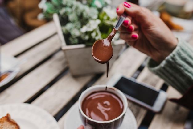 Jonge onherkenbare blanke vrouw die geniet van een warme chocolademelk op een terras met vrienden