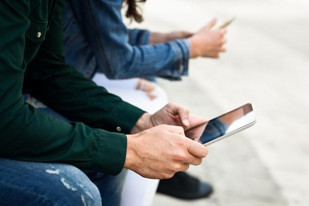 Jonge onherkenbare mensen die smartphone en tabletcomputer gebruiken