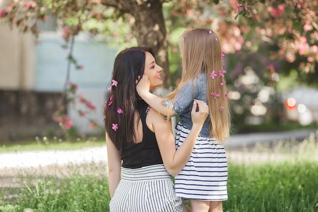 Jonge onherkenbare vrouw met haar kleine dochter die zich in het park met bloemen in hun haar bevindt. moeder en meisje buitenshuis. gelukkig gezin.