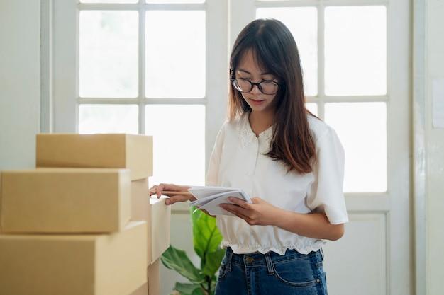 Jonge online verkoper die bestelling van klant controleert en pakketdoos voorbereidt die aan klanten levert