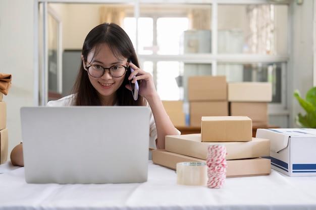 Jonge online verkoper die op telefoon spreekt om orde van klanten te ontvangen en te controleren