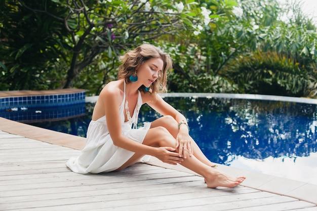 Jonge onschuldige puur mooie vrouw die droomt, zittend aan het zwembad in witte jurk, romantisch, lyrisch, denken, groene tropische natuur, zomer, ontspannen, chillen, lange benen