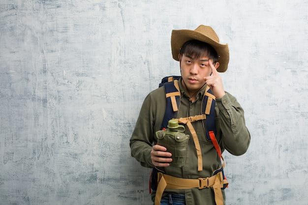 Jonge ontdekkingsreiziger chinese man na te denken over een idee