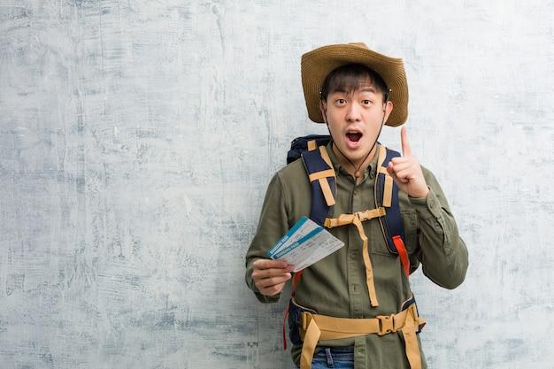 Jonge ontdekkingsreiziger chinese mens die luchtkaartjes houden die een groot idee, van creativiteit hebben