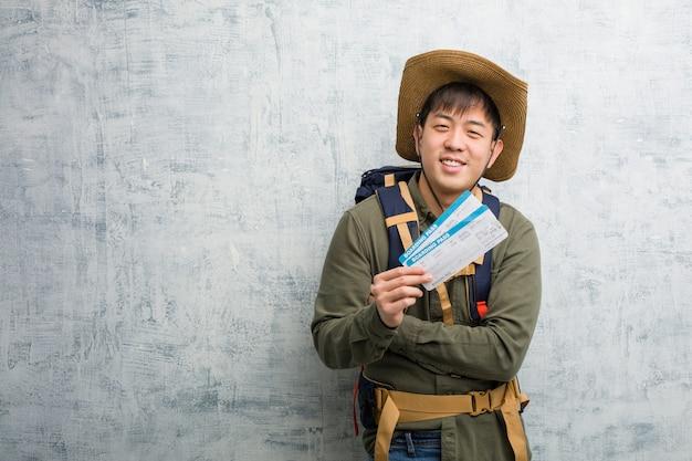 Jonge ontdekkingsreiziger chinese mens die luchtkaartjes houden die zeker glimlachen en wapens kruisen, die omhoog eruit zien