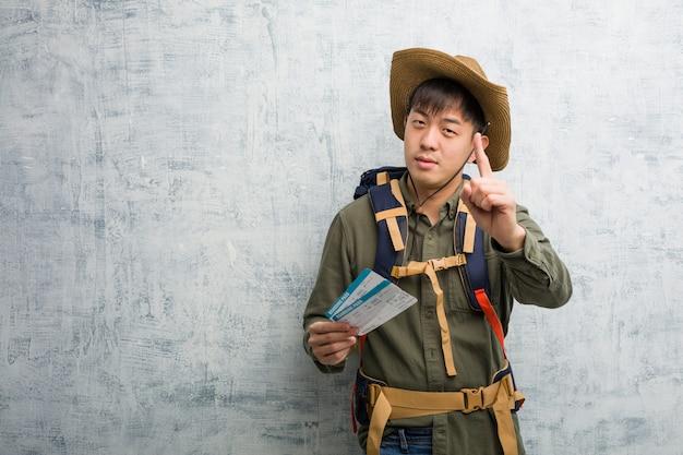 Jonge ontdekkingsreiziger chinese mens die luchtkaartjes tonen die nummer één tonen