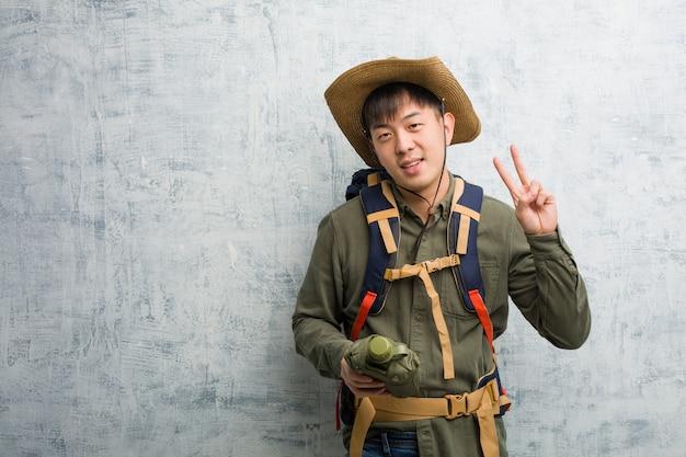 Jonge ontdekkingsreiziger chinese mens die nummer twee toont