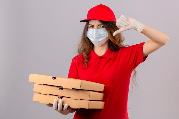 Jonge ontevreden leveringsvrouw met krullend haar die rode poloshirt en pet in medisch beschermend masker en handschoenen dragen die zich met pizzadozen bevinden die afkeer over geïsoleerde witte achtergrond tonen