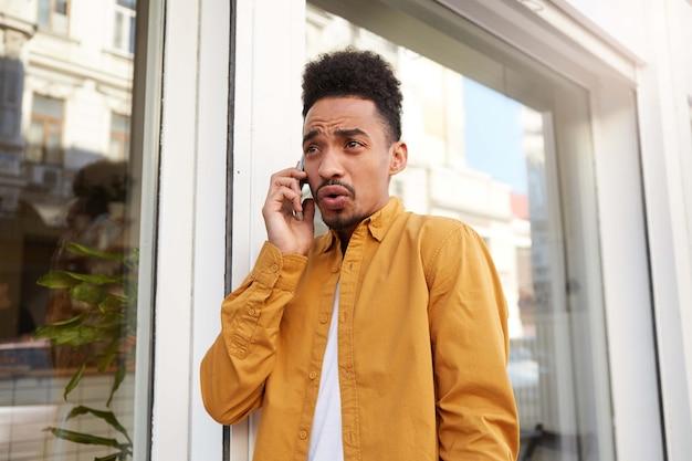Jonge ontevreden man met een donkere huid in een geel overhemd, spreekt aan de telefoon met zijn vrienden en loopt over straat, met een verontwaardigde uitdrukking.
