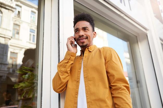 Jonge, ontevreden man met een donkere huid in een geel overhemd, telefoneert met zijn vrienden en loopt over straat, ziet er teleurgesteld uit.