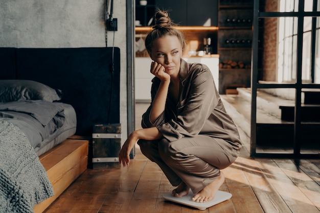 Jonge ontevreden ongelukkige vrouw hurkte 's ochtends over elektronische weegschalen nadat ze wakker werd op de achtergrond van een moderne slaapkamer, ontevreden over haar gewichtsdoelen. dieetconcept