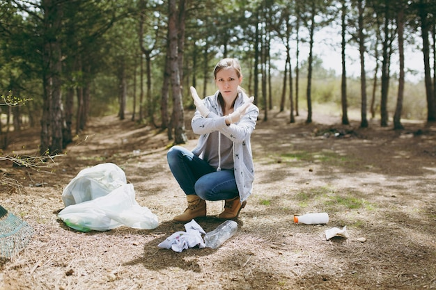 Jonge ontevreden vrouw die afval schoonmaakt en stopgebaar toont met gekruiste handen in de buurt van vuilniszakken in het park. probleem van milieuvervuiling